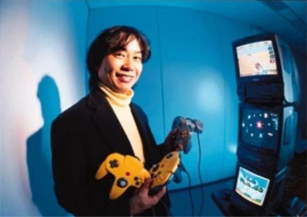 Miyamoto segurando vários controles do Nintendo 64.